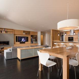 Esempio di una sala da pranzo aperta verso la cucina moderna di medie dimensioni con pareti bianche, parquet scuro e cornice del camino piastrellata