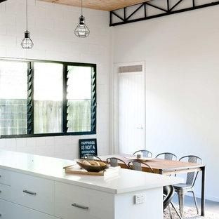 Esempio di una sala da pranzo aperta verso il soggiorno industriale di medie dimensioni con pareti bianche e pavimento in cemento