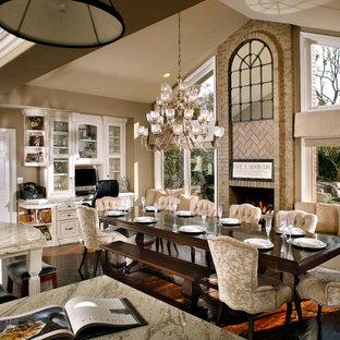 Immagine di una grande sala da pranzo aperta verso il soggiorno classica con pareti beige, parquet scuro, camino classico e cornice del camino in mattoni