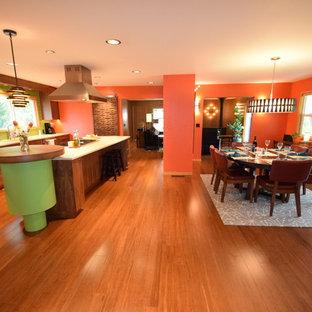 Idées déco pour une grande salle à manger ouverte sur la cuisine rétro avec un mur orange, un sol en bambou, une cheminée d'angle, un manteau de cheminée en brique et un sol marron.
