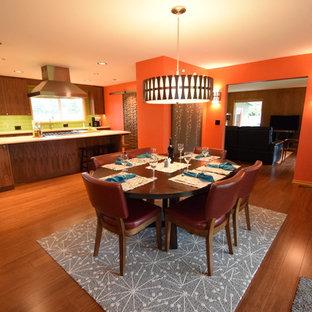 Esempio di una grande sala da pranzo aperta verso la cucina moderna con pareti arancioni, pavimento in bambù, camino ad angolo, cornice del camino in mattoni e pavimento marrone
