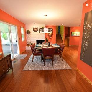 Exemple d'une grande salle à manger ouverte sur la cuisine rétro avec un mur orange, un sol en bambou, une cheminée d'angle, un manteau de cheminée en brique et un sol marron.
