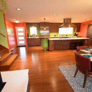 Foto di una grande sala da pranzo aperta verso la cucina minimalista con pareti arancioni, pavimento in bambù, camino ad angolo, cornice del camino in mattoni e pavimento marrone