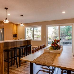 Ejemplo de comedor de cocina bohemio, de tamaño medio, con paredes beige, suelo de madera clara, chimenea tradicional y marco de chimenea de madera