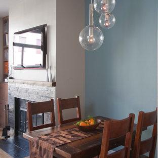 Imagen de comedor minimalista, pequeño, abierto, con suelo de madera clara, paredes azules, chimenea tradicional y marco de chimenea de piedra