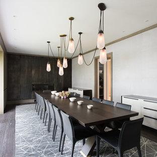 Esempio di una sala da pranzo minimal chiusa con pareti bianche, parquet scuro, camino lineare Ribbon, cornice del camino in legno e pavimento marrone