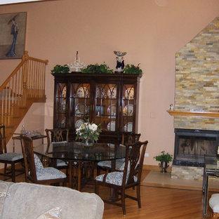 Inspiration pour une salle à manger ouverte sur la cuisine bohème de taille moyenne avec un mur orange, un sol en bois foncé, une cheminée d'angle et un manteau de cheminée en pierre.