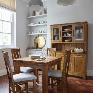 Modelo de comedor de estilo de casa de campo, pequeño, sin chimenea, con paredes grises y suelo de madera oscura