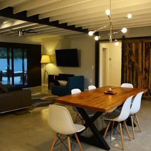 Exemple d'une salle à manger ouverte sur le salon industrielle de taille moyenne avec un mur blanc, béton au sol et aucune cheminée.