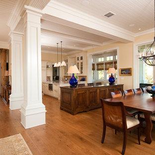Foto di una grande sala da pranzo aperta verso il soggiorno chic con pareti gialle, pavimento in legno massello medio e camino classico