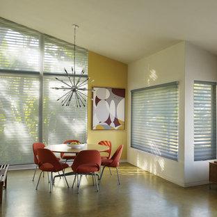 Idee per una sala da pranzo aperta verso la cucina eclettica di medie dimensioni con pareti bianche, pavimento in cemento e pavimento verde