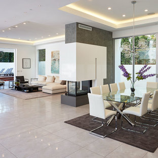 Example of a trendy gray floor great room design in Los Angeles with white walls and a two-sided fireplace