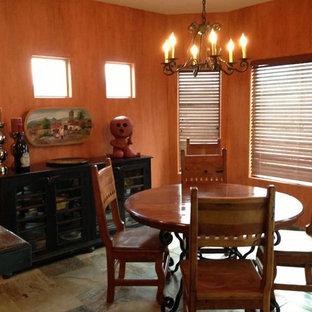 Immagine di una piccola sala da pranzo aperta verso la cucina stile americano con pareti arancioni e pavimento in ardesia