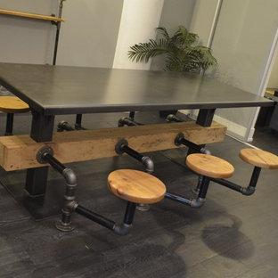 Exemple d'une salle à manger ouverte sur la cuisine industrielle de taille moyenne avec un mur gris, un sol en bois foncé, aucune cheminée et un sol marron.