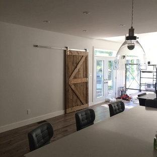Ispirazione per una sala da pranzo aperta verso la cucina stile rurale di medie dimensioni con pareti bianche, parquet chiaro, nessun camino e pavimento marrone