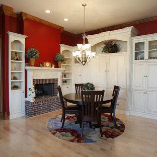 Ispirazione per una piccola sala da pranzo aperta verso la cucina chic con pareti rosse, parquet chiaro, camino classico e cornice del camino in mattoni