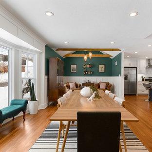 Idee per una sala da pranzo aperta verso il soggiorno chic di medie dimensioni con pareti bianche, pavimento in legno massello medio, camino classico e cornice del camino in mattoni