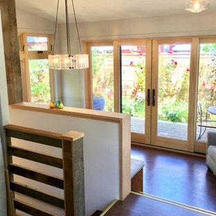 Cette image montre une petite salle à manger ouverte sur la cuisine rustique avec un mur gris, un sol en liège et un sol marron.