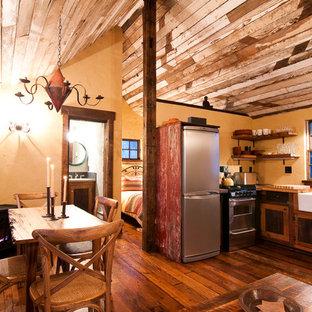 Immagine di una piccola sala da pranzo rustica con pareti gialle