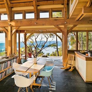 Idee per una piccola sala da pranzo aperta verso il soggiorno stile rurale con pareti gialle e pavimento in ardesia