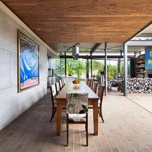 Cette image montre une salle à manger ouverte sur le salon design avec un sol en brique.