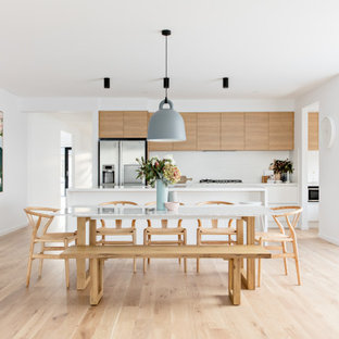 This is an example of a scandinavian open plan dining in Melbourne with white walls, light hardwood floors and beige floor.