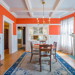 Example of a classic medium tone wood floor enclosed dining room design in San Francisco with orange walls, a standard fireplace and a tile fireplace