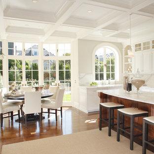 Immagine di una grande sala da pranzo aperta verso la cucina minimal con pareti bianche, parquet scuro e nessun camino