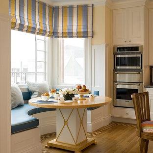 Immagine di una grande sala da pranzo aperta verso la cucina chic con pareti gialle, pavimento in legno massello medio e pavimento marrone