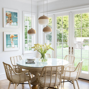 Example of a large transitional light wood floor and beige floor dining room design in New York with white walls