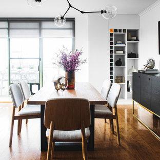 Foto di una sala da pranzo aperta verso il soggiorno eclettica di medie dimensioni con pareti bianche, pavimento in laminato e nessun camino