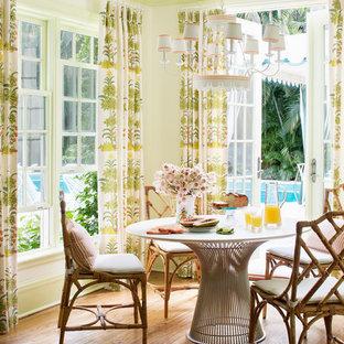 Ejemplo de comedor tropical con paredes verdes y suelo de madera en tonos medios