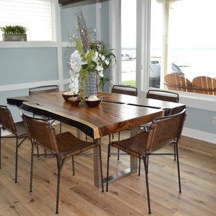 Aménagement d'une salle à manger ouverte sur la cuisine classique de taille moyenne avec un mur bleu, un sol en vinyl, une cheminée standard, un manteau de cheminée en pierre et un sol multicolore.