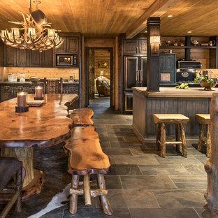 Foto di una grande sala da pranzo aperta verso il soggiorno rustica con pavimento in ardesia, pareti marroni e pavimento grigio