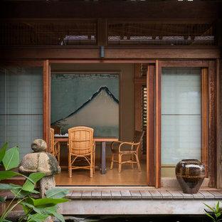 Réalisation d'une grand salle à manger asiatique fermée avec un mur beige, aucune cheminée, un sol en bois brun et un sol marron.