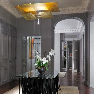 Cette photo montre une grand salle à manger éclectique avec un mur gris et un sol en bois foncé.