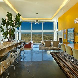 ソルトレイクシティの中サイズのコンテンポラリースタイルのおしゃれなダイニング (黄色い壁、コンクリートの床、標準型暖炉、金属の暖炉まわり、グレーの床) の写真