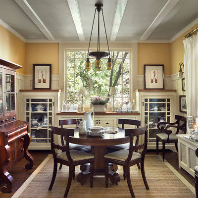 Example of a classic dark wood floor enclosed dining room design in New York with yellow walls