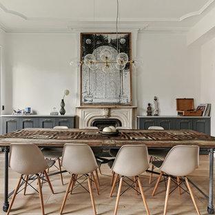 Foto de comedor ecléctico, de tamaño medio, cerrado, con paredes blancas, suelo de madera clara, chimenea tradicional, marco de chimenea de piedra y suelo beige