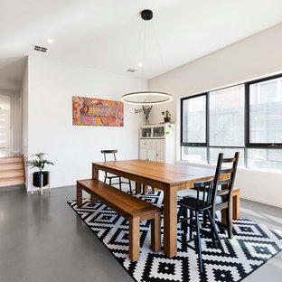 Inspiration for a large scandinavian dining room in Melbourne with white walls, grey floor and no fireplace.