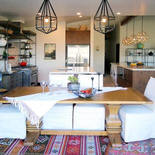 Foto de comedor ecléctico, grande, abierto, con paredes blancas, suelo de madera en tonos medios, chimenea tradicional, marco de chimenea de hormigón y suelo marrón