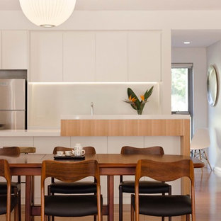 This is an example of a contemporary kitchen/dining combo in Sydney with white walls, medium hardwood floors and brown floor.