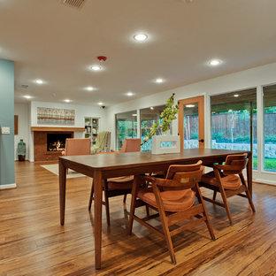 Diseño de comedor vintage, grande, abierto, con paredes blancas, suelo de bambú, chimenea tradicional y marco de chimenea de ladrillo