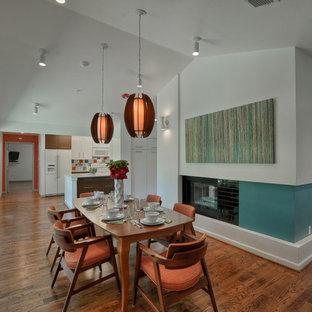 Idéer för mellanstora 60 tals matplatser med öppen planlösning, med vita väggar, mörkt trägolv, en dubbelsidig öppen spis och en spiselkrans i trä