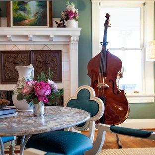 Immagine di una sala da pranzo aperta verso il soggiorno design di medie dimensioni con pareti verdi, pavimento in legno massello medio, camino classico e cornice del camino in cemento
