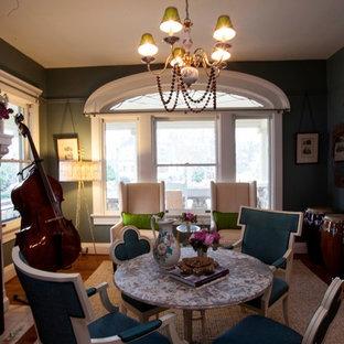Idee per una sala da pranzo aperta verso il soggiorno minimal di medie dimensioni con pareti verdi, pavimento in legno massello medio, camino classico e cornice del camino in cemento