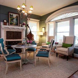 Immagine di una sala da pranzo aperta verso il soggiorno minimal di medie dimensioni con pareti verdi, pavimento in legno massello medio, camino classico e cornice del camino in cemento