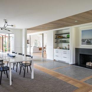 Modelo de comedor actual, extra grande, cerrado, con paredes blancas, suelo de madera en tonos medios, chimenea tradicional, marco de chimenea de hormigón y suelo marrón