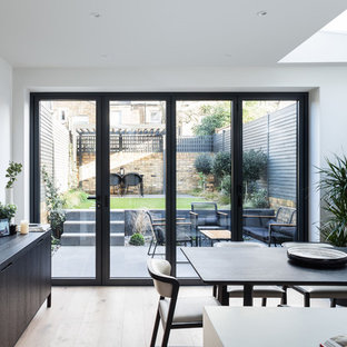 Large contemporary kitchen/dining room in London with white walls, light hardwood flooring and no fireplace.