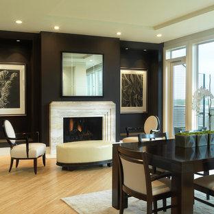 Ispirazione per una sala da pranzo tradizionale con pareti nere, pavimento in legno massello medio e camino classico